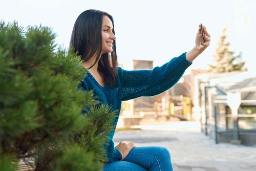 Pleasant woman doing self-photo outdoors close to a small conifer