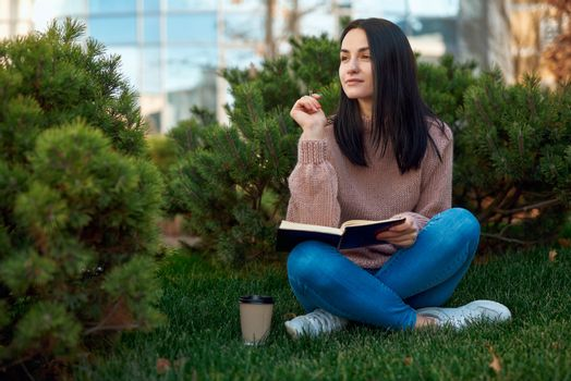 Pleasant female student sitting on grass with her leggs crossed and holding pen and notebook