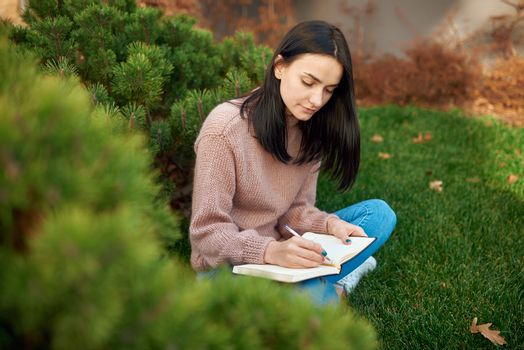 Pleasant young brunette with long hair is concentrated on writing on page of her notebook outside on an open lawn