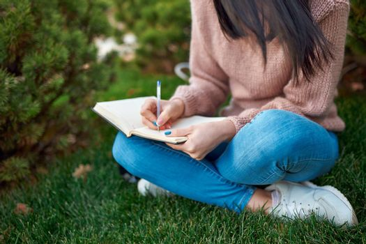Close up of a young woman in jeans and sweater taking some notes in her paper planner while sitting on grass outdoors