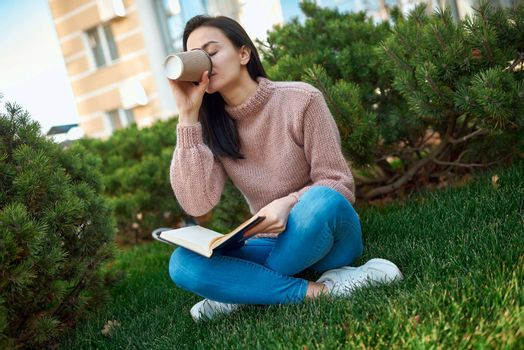 Charming young lady drinking latte from a paper glass and putting down the copybook while sitting on green grass in a dooryard