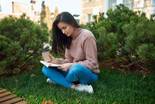Attractive concentrated young woman with interesting book sitting cross-legged on a grass outside of modern city constructions