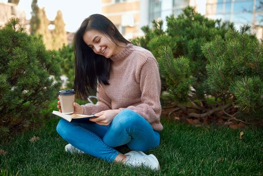 Adorable young lady enjoying an exciting novel and spending time with it outdoors on a green grass lawn