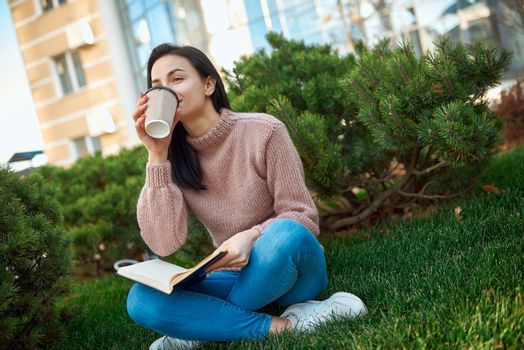 Pretty young woman with a thick daybook on her knees enjoying hot drink on a green lawn near tall modern building