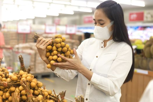 Asian woman long hair wearing protective face mask  in supermarket department store. Female, looking grocery to buy  some fruit. New normal after covid-19. Family concept.