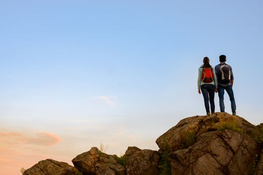 Couple of Young Travelers with Backpacks Standing on the Top of the Rock in the Evening. Family Travel and Adventure Concept.