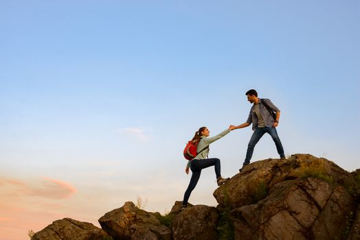 Couple of Young Happy Travelers with Backpacks Hiking in the Mountains at the Evening. Man Helping Woman to Climb to the Top of the Rock. Family Travel and Adventure Concept.