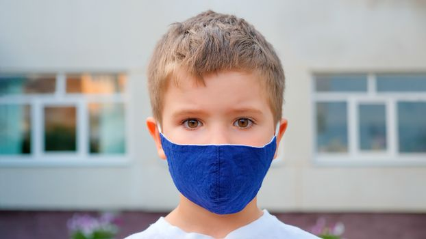 Face mask for protection coronavirus outbreak. Child wearing a medicine mask outdoors. Coronavirus epidemic. Boy with protection facemask. Coronavirus quarantine. Health care. Back to school