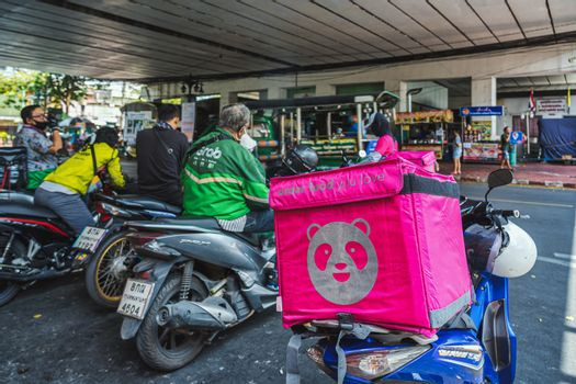 BANGKOK, THAILAND - APRIL 2020 : Various food delivery box on the motorcycles include Food Panda, Grab and Get food at Food delivery service point on April 17, 2020, Bangkok,Thailand, Covid outbreak