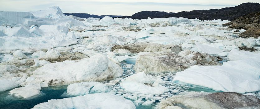 Climate Change and Global Warming - Icebergs and from melting glacier in icefjord in Ilulissat, Greenland. Panoramic banner photo of arctic nature ice landscape.