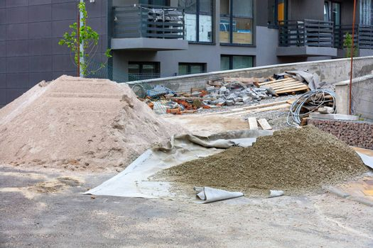 A workplace at a construction site with a pile of sifted sand and cement for laying paving slabs in the background of a new residential building under construction in blur.