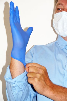 masked doctor puts on medical gloves close up