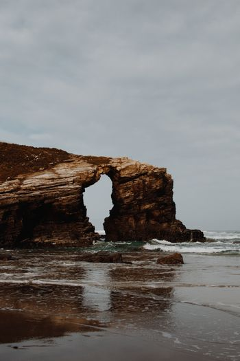 A giant rock forming an eye in the beach