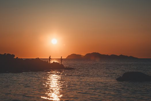 Fishermen in the sea under a clear sunset