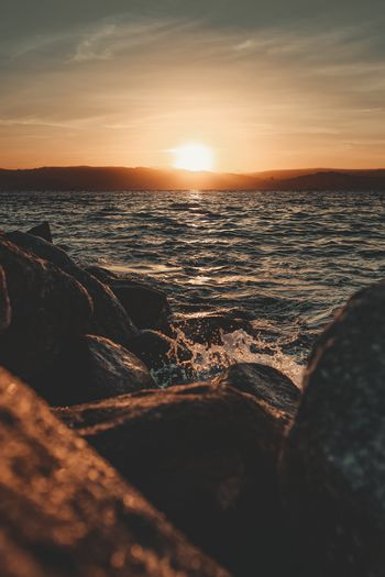 The sea splashing against the rocks of the shore during a sunrise