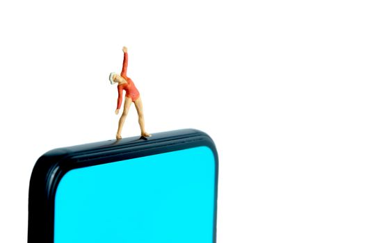 Yoga trainer app. A women doing exercise above smartphone. Miniature people figure conceptual photography.