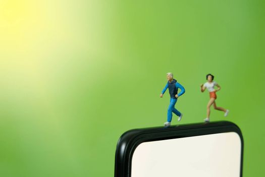 Running and jogging tracking app concept. A men and women running above smartphone. Miniature people figure photography.