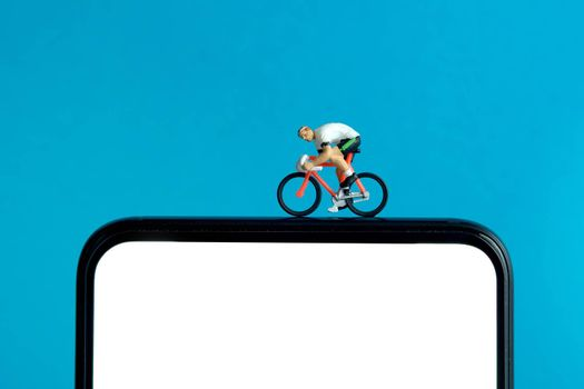 Bike cycling trainer and tracing app. A cycling above smartphone. Miniature people figure conceptual photography.
