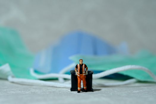 Cleaning workers carry disposable mask rubbish that has been used in the trash bin. Medical waste conceptual photo. Miniature people photography.
