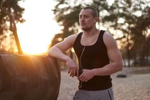 Young adult caucasian athlete listening phone music white headphones after workout. Handsome sportsman resting after cross training exercises sunset background. Healthy lifestyle concept.