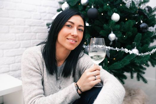 A young woman sits near a Christmas tree, holding a glass with white wine and a Christmas toy. Preparation for the New Year's celebration.