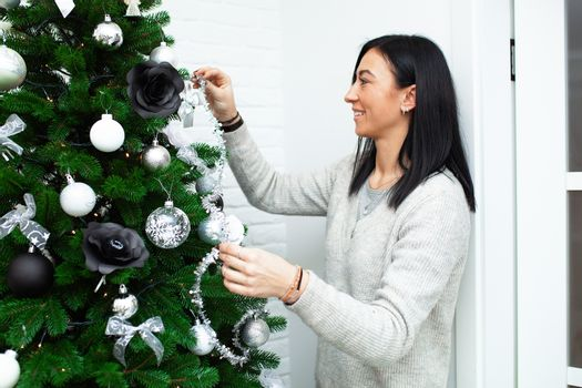 A young woman decorate the Christmas tree, preparing for the New Year's celebration. Female decorate a Christmas tree. Beautiful girl are smiling and have fun during the Christmas holidays.
