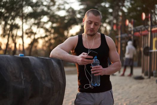 Young adult caucasian athlete listening phone music white headphones after workout. Handsome sportsman resting after cross training exercises sunset background. Healthy lifestyle concept. Drink water