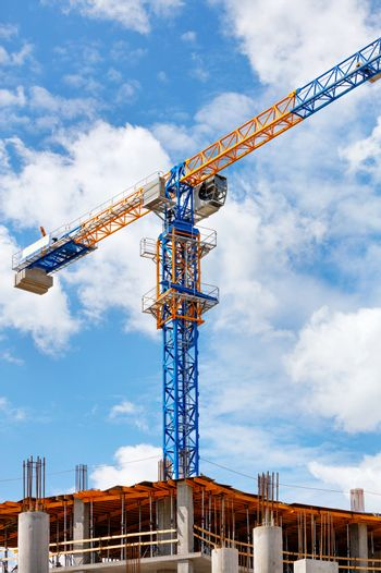 The arrow of a yellow and blue high-rise tower crane rises above the construction site diagonally against a background of blue sky and white clouds, copy space.