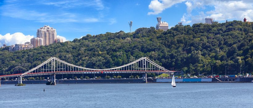 Pedestrian bridge in Kyiv, view panorama of the city of Kyiv, on Dnipro river, sailboat, Ukraine.