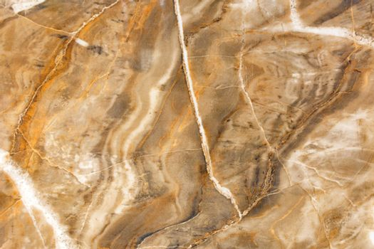 Unusual texture of old brown marble with beige spots, cracks and scratches. Polished surface.