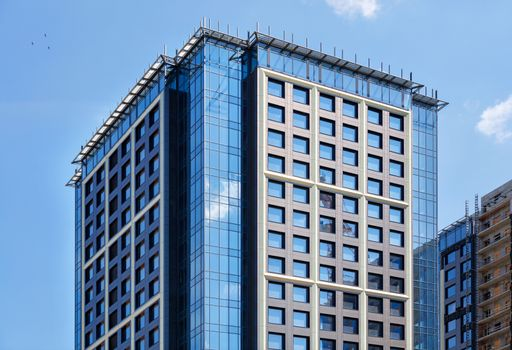 Fragment of the symmetrical facades of modern high-rise residential buildings of glass and concrete, updating the old residential areas of the city, the windows reflect the blue sky and the crane.