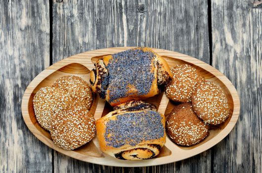 Butter appetizing buns with poppy seeds and sesame cookies on a wooden oval board on an old wooden table, rustic style, copy space.