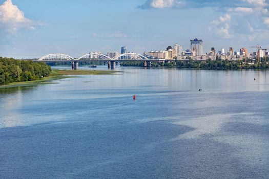 The water surface of the wide Dnipro River in the foreground, immersed in the green of the banks, a white railway bridge and new residential areas of Kyiv on the horizon, copy space.