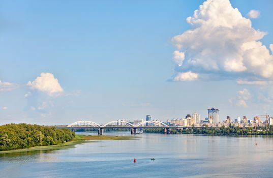 Over the water surface of the wide Dnipro River, large figured cloud illuminated by sunlight floated in the blue sky, skirting the white railway bridge and new residential quarters of Kyiv, copy space.