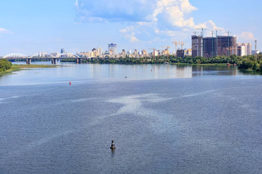 A beautiful cityscape with a view of the Dnipro River in the foreground and new residential areas under construction in the city of Kyiv on the horizon.