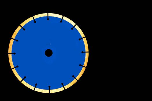 Diamond blue cutting disc for cutting concrete and reinforced concrete with even segments in a circle on a black isolated background, close-up, copy space.