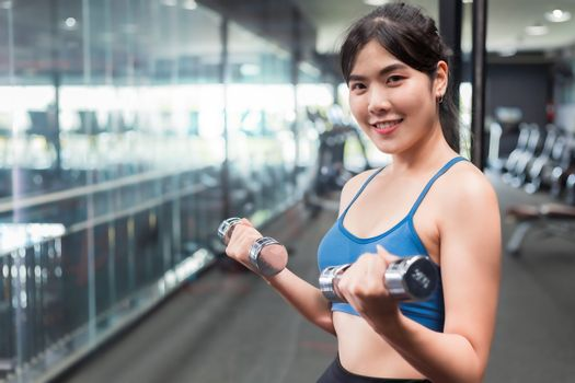 Asian woman Bodybuilder with dumbbell weights power athletic exercises.Metaphor Fitness and workout concept exercise Health lifestyle muscle body with take care of your health
