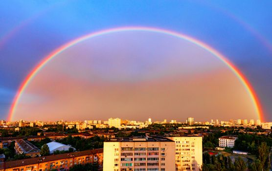 Panorama of an urban residential area and a huge rainbow illuminated by the sun against the backdrop of the evening sky.