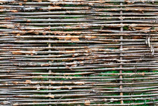 Texture and background of a wicker fence made of old weathered branches, copy space.