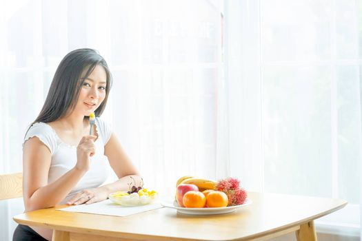 Beautiful pregnant woman hold folk with some fruits and sit near table with various types of fruits in front of curtain with morning light. Concept of good and healthy food for pregnant people.