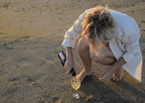 drunk woman pours champagne into a glass by the sea.