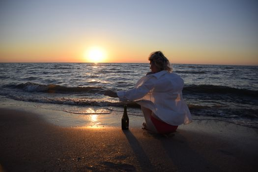Young girl on the sea beach with a bottle of champagne and a glass, the blonde is drinking champagne at the sea. woman is sitting on the sand at the beach.