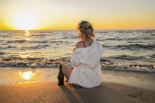 Girl with a glass and a bottle of champagne sits on the seashore.