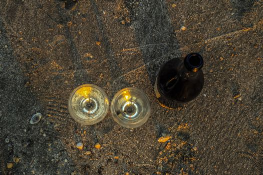 a bottle of champagne and glasses stand on the sand of the seashore.