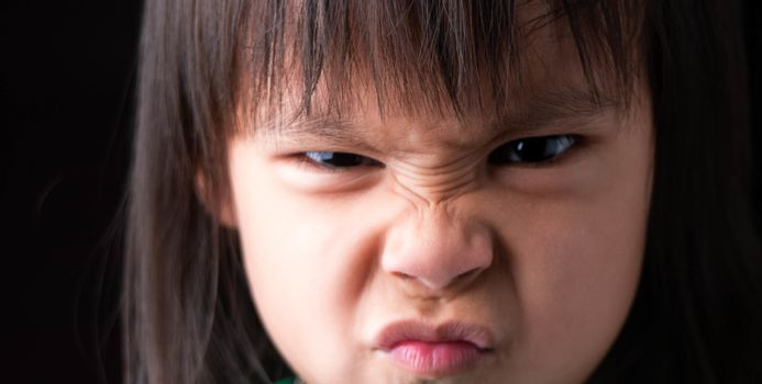 Portrait of child face with angry expression.