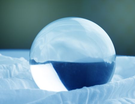 Crystal glass ball sphere transparent on blue gradient background.