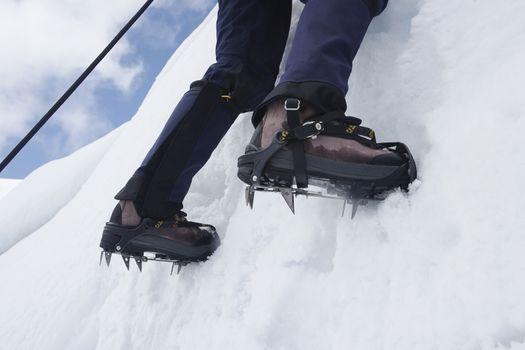 Close up photo of mountain climber reaching snowy peak