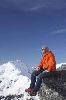 Mountain climber sitting on edge of mountain peak