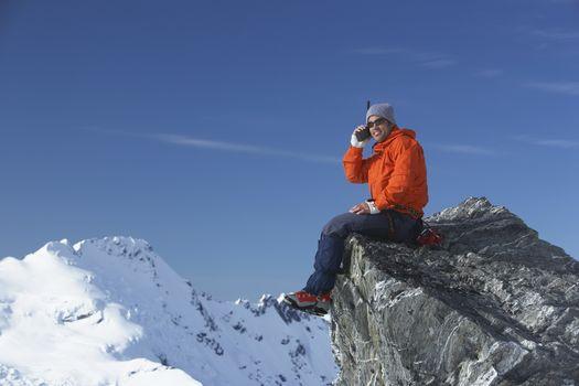 Mountain climber using walkie-talkie on mountain peak