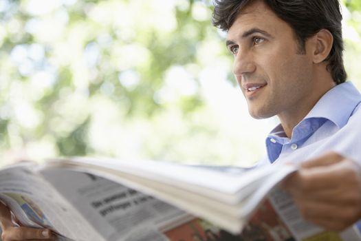 Portrait of mid adult man reading newspaper